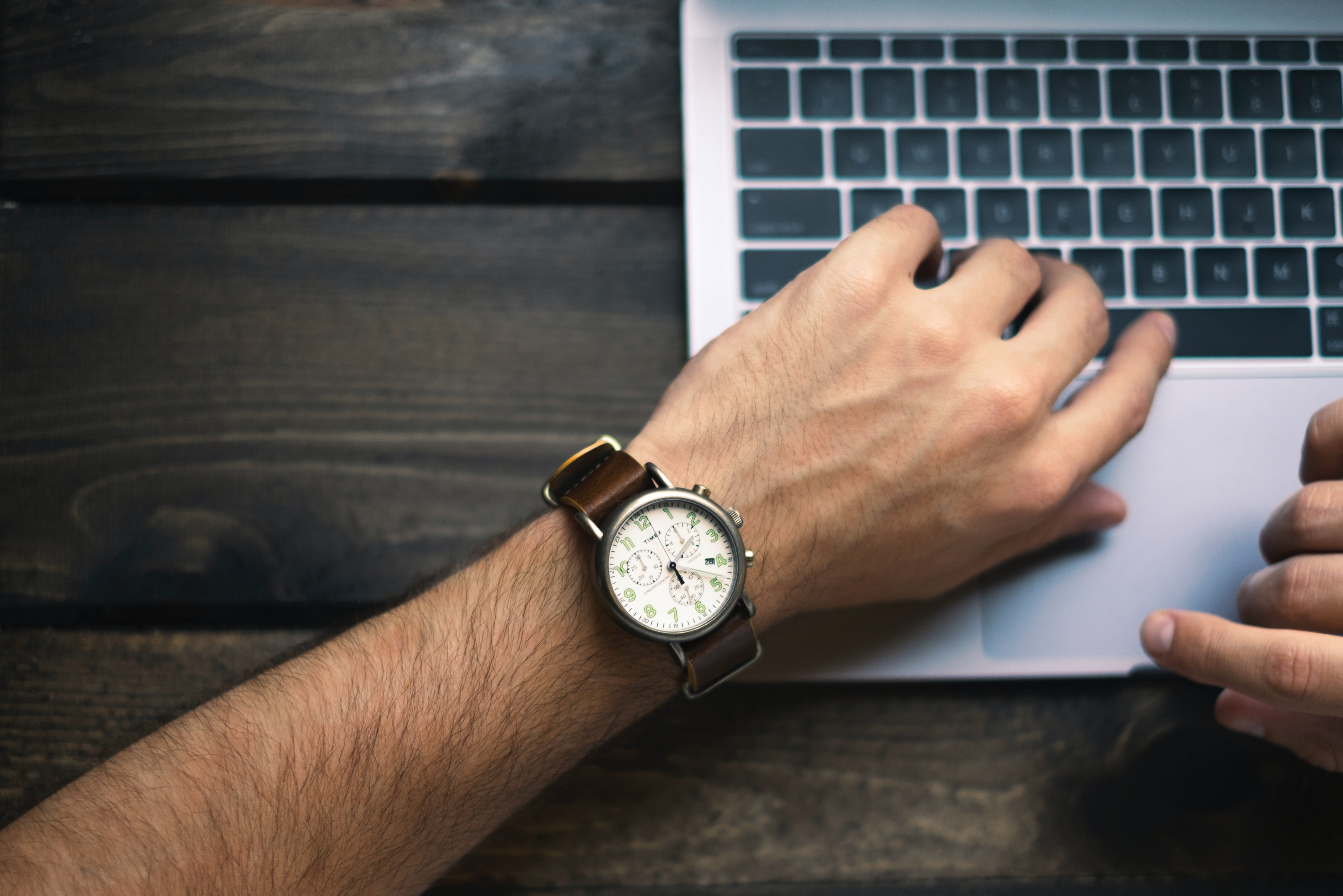 Laptop user looking at watch